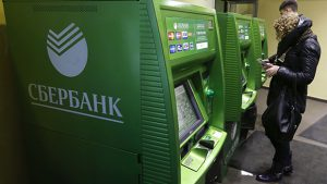 People use an automated teller machine inside a branch of Sberbank in St. Petersburg, November 5, 2014. Russia's central bank took a major step towards floating the rouble on Wednesday by limiting its daily interventions, accelerating a slide in the Russian currency.  REUTERS/Alexander Demianchuk (RUSSIA  - Tags: BUSINESS)